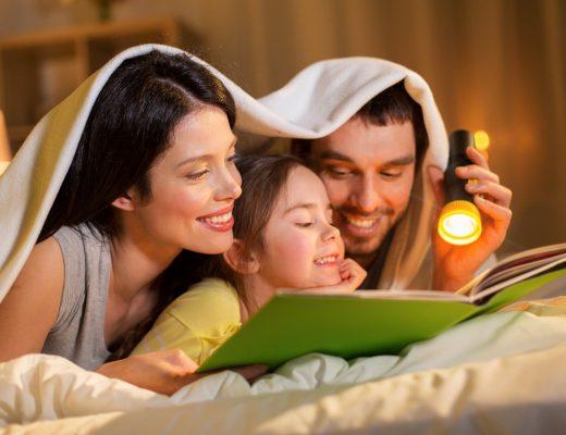 Aile içi iletişimde kilit noktalar: yatakta çocuklarıyla kştap okuyan mutlu anne ve baba