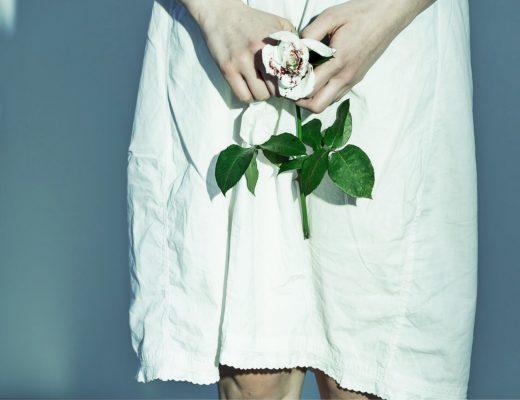 Sızı. Kadına şiddeti resmeden elinde kana bulanmış beyaz bir gül tutan kadın fotoğrafı
