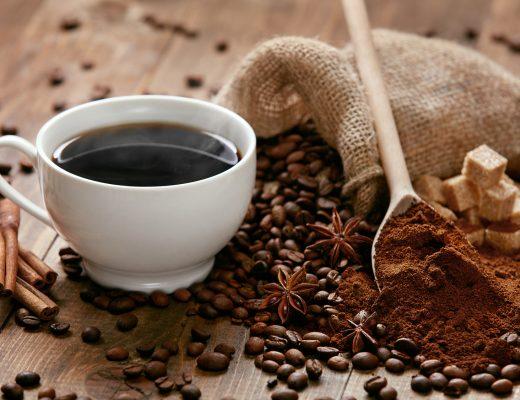 Bir fincan kahve ve dökülmüş kahve çekirdekleri