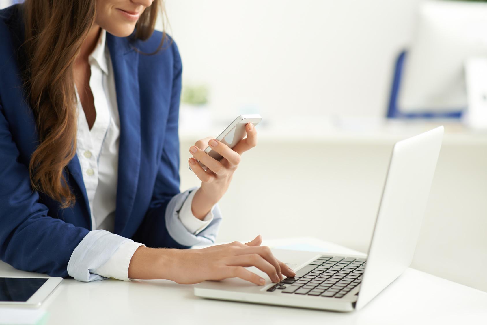 Teknoloji Bağımlılığı başlıklı yazı için bir elinde bilgisayar, diğerinde akıllı telefon olab bir iş kadını fotoğrafı