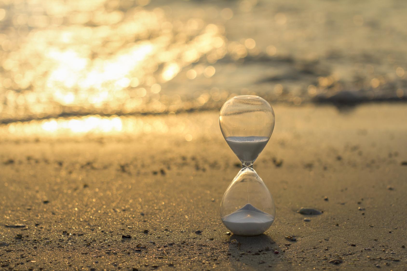 Hayatı ve zamanı tüketiyoruz. Sahilde akan bir kum saati fotoğrafı.